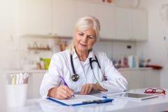 Doutor que escreve uma prescrição fotos de stock