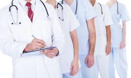 Doutor que está na prescrição da escrita do grupo fotografia de stock