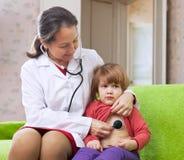 Doutor que examina 2 anos de bebê Imagem de Stock