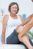 Doutor que examina seu joelho dos pacientes Fotografia de Stock Royalty Free