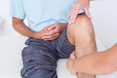 Doutor que examina seu joelho paciente fotografia de stock