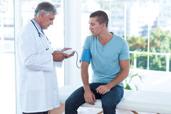 Doutor que examina sua pressão sanguínea dos pacientes fotografia de stock
