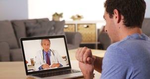 Doutor que fala ao paciente sobre a câmara web imagem de stock