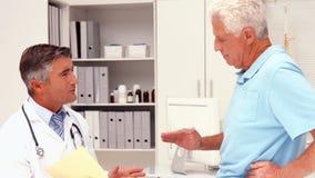 Doutor que fala com o paciente ferido video estoque
