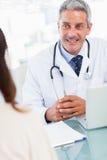 Doutor que fala com seu paciente Imagens de Stock