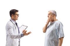 Doutor que fala com um paciente idoso interessado fotos de stock