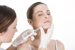 Doutor que faz a injeção do botox a uma mulher foto de stock royalty free