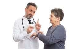 Doutor que guarda a caneca de café e que mostra o gesto ocupado ao paciente foto de stock royalty free