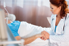 Doutor que guarda a mão do paciente fotos de stock