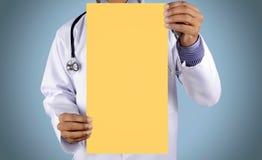 Doutor que guarda o cartão com estetoscópio Fotografia de Stock