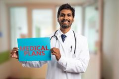 Doutor que guarda o papel com texto dos planos médicos fotos de stock