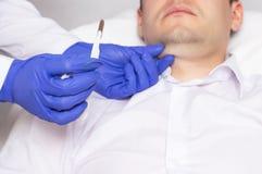 Doutor que guarda um escalpelo cirúrgico no fundo da cara de um homem com um queixo dobro Conceito da cirurgia plástica fotos de stock royalty free