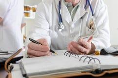 Doutor que guarda um smartphone e que toma notas Fotos de Stock