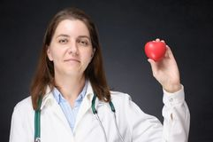 Doutor que guarda uma forma vermelha do coração Fotografia de Stock