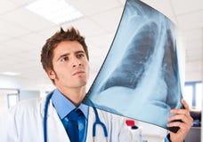 Doutor que guardara uma radiografia Fotos de Stock Royalty Free