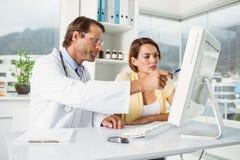 Doutor que mostra algo no tela de computador ao paciente Fotografia de Stock Royalty Free