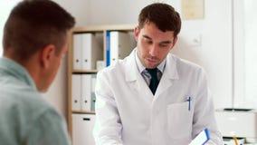 Doutor que mostra o cardiograma ao paciente no hospital vídeos de arquivo