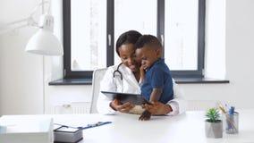 Doutor que mostra o PC da tabuleta ao paciente do bebê na clínica video estoque
