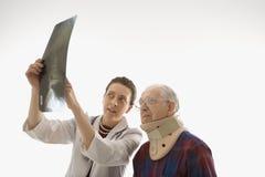 Doutor que mostra o raio X paciente. Fotos de Stock