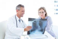 Doutor que mostra o raio X a seu paciente Foto de Stock Royalty Free