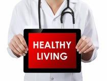 Doutor que mostra a tabuleta com texto VIVO SAUDÁVEL Fotos de Stock