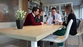 Doutor que mostra a varredura do ultrassom aos pares felizes no centro clínico video estoque
