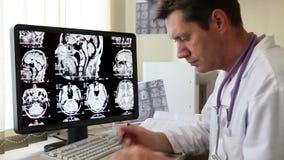Doutor que olha a varredura do CT filme