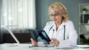 Doutor que olha a varredura, raio X de exame dos pulmões pacientes, cuidados médicos, medicina fotografia de stock
