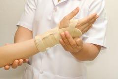 Doutor que põe a cinta do pulso Fotos de Stock Royalty Free