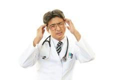 Doutor que tem uma dor de cabeça fotografia de stock royalty free