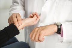 Doutor que toma o pulso do paciente. fotografia de stock royalty free