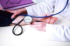 Doutor que toma a pressão sanguínea Foto de Stock Royalty Free