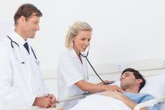 Doutor que toma a pulsação do coração de seu paciente fotos de stock