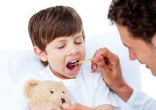 Doutor que toma a temperatura do rapaz pequeno Foto de Stock Royalty Free