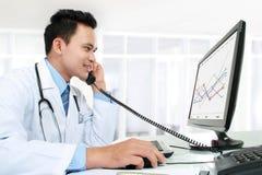Doutor que trabalha com seu computador imagem de stock