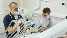 Doutor que usa o microscópio Dentista que trata o paciente na clínica dental moderna O Orthodontist trabalha com um assistente E video estoque