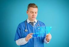 Doutor que usa o tablet pc de vidro futurista fotografia de stock