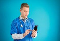 Doutor que usa o telefone celular foto de stock