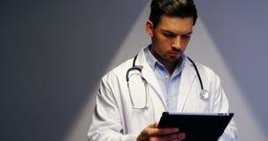 Doutor que usa a tabuleta digital no corredor vídeos de arquivo