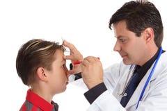 Doutor que verific os olhos pacientes Fotografia de Stock Royalty Free