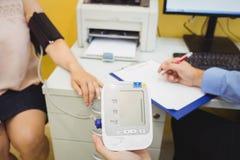 Doutor que verific a pressão sanguínea do paciente fotos de stock royalty free