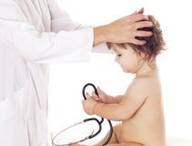 Doutor que verifica a cabeça do bebê no fundo branco Foto de Stock
