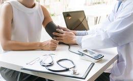 Doutor que verifica a pressão sanguínea arterial paciente da mulher adulta Healt Imagens de Stock