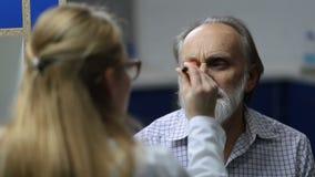 Doutor que verifica a sintomatologia do olho com a lanterna elétrica filme