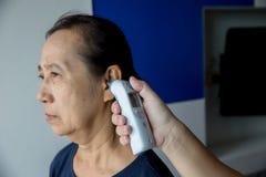 Doutor que verifica a temperatura do paciente na orelha com o termômetro timpânico, dentro do hospital ou da clínica foto de stock