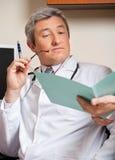 Doutor Reading Medical Report fotos de stock royalty free