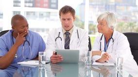 Doutor sério que fala com seus colegas sobre um PC da tabuleta video estoque