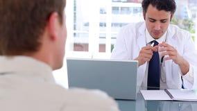 Doutor sério que fala a seu paciente ao sentar-se vídeos de arquivo