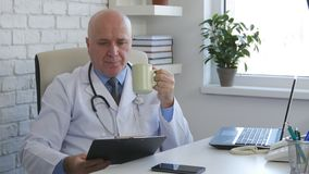 Doutor seguro Enjoy um copo do chá e de documentos lidos imagens de stock