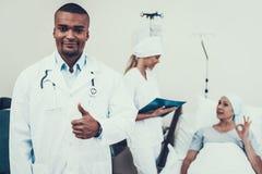 Doutor Shows Thumbs-Up Paciente do fundo posing imagens de stock